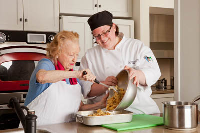 Watermark chef helping a resident cook a meal