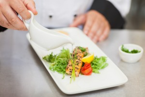 Chef pouring sauce on salmon dish