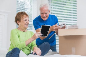 A senior couple moving house, packing a cardboard box in the bedroom. They are talking and smiling, looking at a picture frame which is bringing back memories.